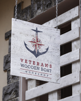 Veterans Wooden Boat Workshop logo on a rustic white hanging sign